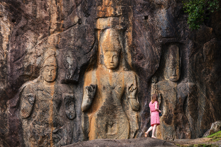 Female tourist visiting Buduruwagala temple with well preserved carvings on the wall in Wellawaya Sri Lanka
