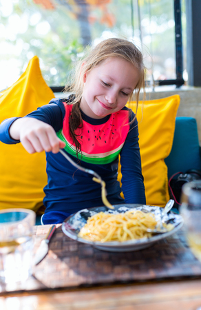 Portrait of adorable girl eating spaghetti for a lunch at restaurant