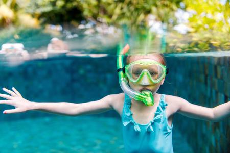 Split underwater photo of adorable little girl at luxury resort swimming pool having fun during summer vacation