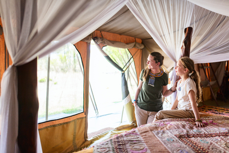 Family mother and her child in safari tent enjoying vacation in Africa