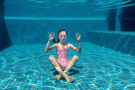 Underwater photo of playful girl in pool practicing yoga