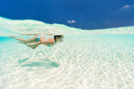 Split underwater photo of a little girl swimming in tropical ocean Stock Photo