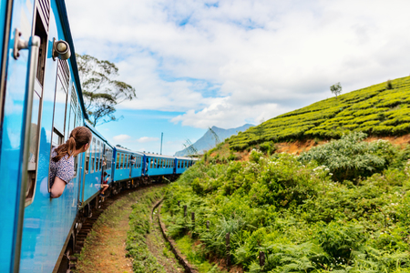 Young woman enjoying train ride from Ella  to Kandy among tea plantations in the highlands of Sri Lanka Stock Photo
