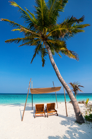 Wooden lounge chairs on a beautiful tropical beach at Maldives Banco de Imagens