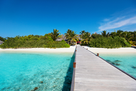 Wooden pathway leading to beautiful tropical island Фото со стока