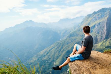 Young man enjoying breathtaking views over mountains and tea plantations from Little Adams peak in Ella Sri Lanka