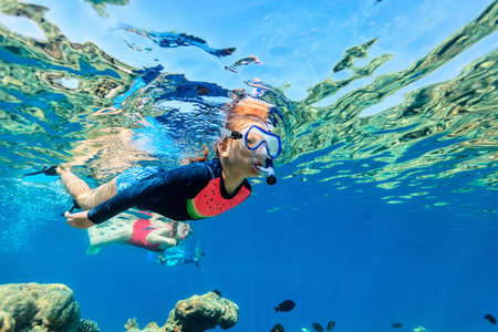 Underwater photo of a girl and her family snorkeling in a clear tropical water at coral reef