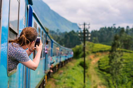 Young woman enjoying train ride from Ella  to Kandy among tea plantations in the highlands of Sri Lanka Фото со стока