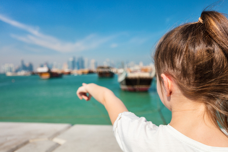 Back view of little girl enjoying panoramic view of Doha Qatar waterfront on sunny day