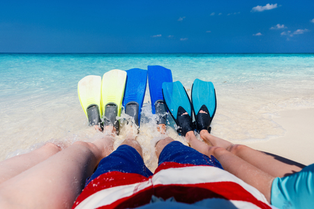 Family legs with fins at shallow water on tropical beach