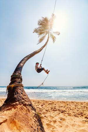 Cute teenage boy having fun swinging on a rope at tropical island beach in Sri Lanka Stockfoto