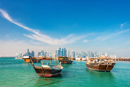 Waterfront in Doha Qatar with traditional wooden small ships known as dhow and city skyline