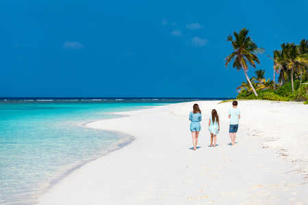 Back view of family mother and kids enjoying tropical beach vacation Stock Photo