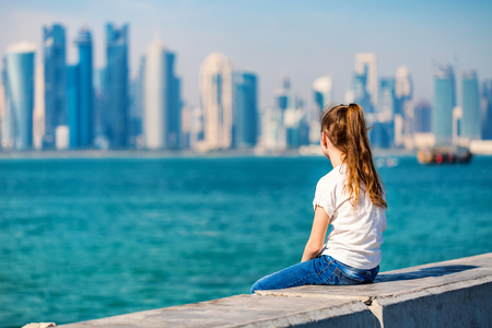 Back view of little girl enjoying panoramic view of Doha Qatar skyline on sunny day