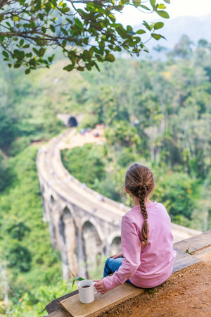 Cute girl enjoying a view over Nine Arches bridge in Demodara one of the iconic landmarks in Sri Lanka