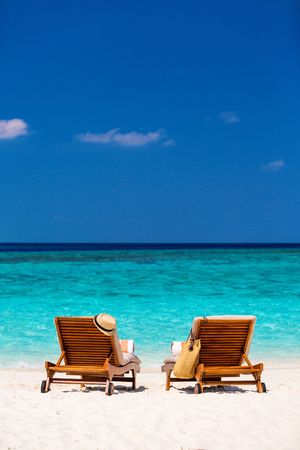 Wooden lounge chairs on a beautiful tropical beach at Maldives 스톡 콘텐츠