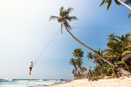 Young man having fun swinging on a rope at tropical island beach in Sri Lanka