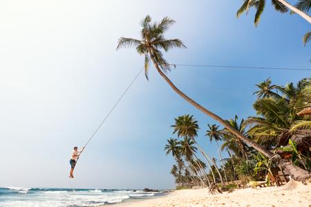 Young man having fun swinging on a rope at tropical island beach in Sri Lanka
