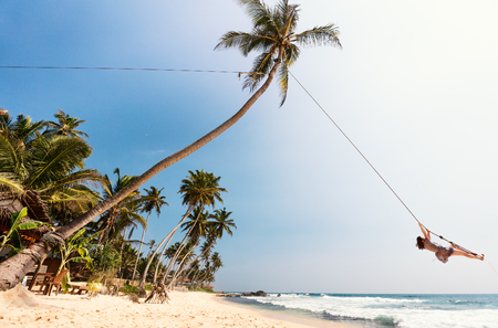 Young woman having fun swinging on a rope at tropical island beach in Sri Lanka