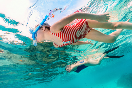Underwater photo of family mother and daughter snorkeling in a clear tropical water at coral reef Banco de Imagens