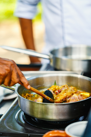 Preparation of traditional Sri Lankan curry dish with tender chicken breast at cooking class Stock Photo