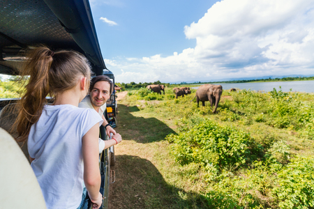 Familia de padre e hija viendo elefantes en el Parque Nacional Udawalawe en Sri Lanka Foto de archivo - 96012810