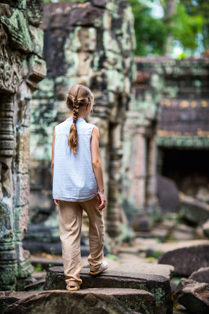 Little girl at ancient Preah Khan temple in Angkor Archaeological area in Cambodia Фото со стока