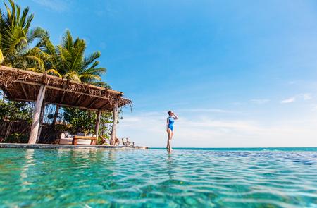 Young beautiful woman walking along infinity pool at tropical resort