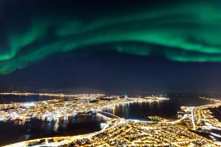 信じられないほどのオーロラオーロラは、北ノルウェーのトロムソの町の上に活動