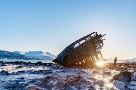 Teenage boy exploring shipwrecked wooden viking boat in Northern Norway