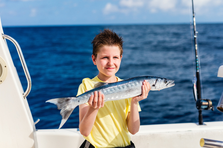 Lucky teenage boy holding barracuda proud with the catch on boat deck