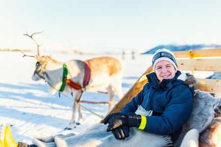 Teenage boy and his family sledding at reindeer safari on sunny winter day in Northern Norway Stock Photo