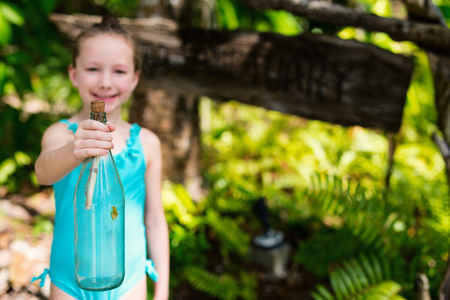 Casual portrait of little girl outdoors on summer day holding treasure bottle 写真素材