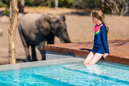 Little girl on African safari vacation enjoying wildlife viewing standing near swimming pool
