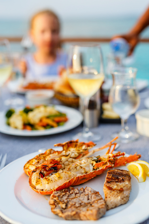 Close up of delicious grilled seafood platter served with white wine for dinner