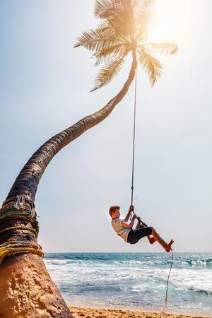 Cute teenage boy having fun swinging on a rope at tropical island beach in Sri Lanka Stock fotó