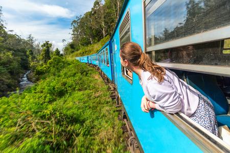 Giovane donna che gode del viaggio in treno da Ella a Kandy tra le piantagioni di tè negli altopiani dello Sri Lanka Archivio Fotografico