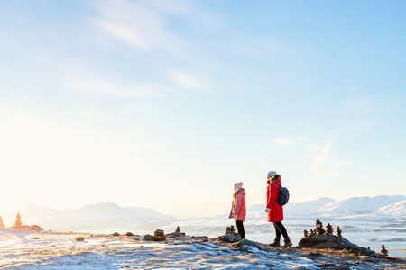 Beautiful family of mother and daughter enjoying snowy winter day outdoors in Northern Norway