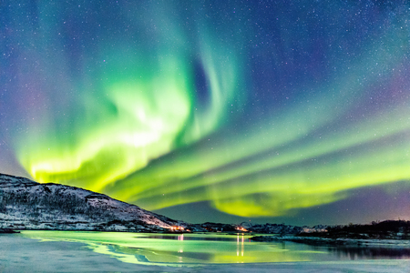 Incredible Northern lights Aurora Borealis activity above the coast in Norway Imagens - 99017858
