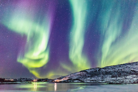 Incredible Northern lights Aurora Borealis activity above the coast in Norway Reklamní fotografie - 99057081