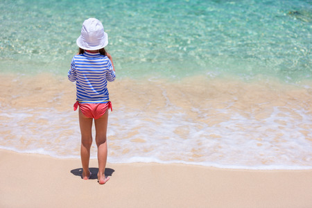 Little girl in a colorful sun protection swimwear on vacation at tropical beach Archivio Fotografico