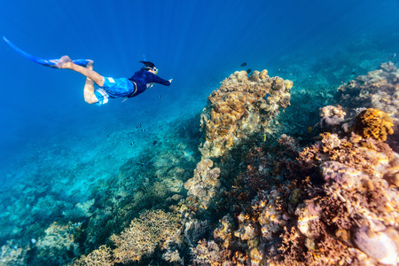 Underwater photo of a young man snorkeling free diving at coral reef in tropical ocean Imagens