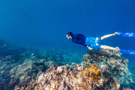 Underwater photo of a young man snorkeling free diving at coral reef in tropical ocean 免版税图像