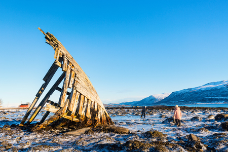 Kids exploring shipwrecked wooden viking boat in Northern Norway Stock Photo