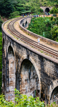 Spectacular view over Nine Arches bridge in Demodara one of the iconic landmarks in Sri Lanka with woman walking along the rails
