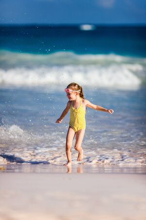 Cute little girl at tropical beach during summer vacation