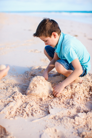 Boy playing with sand at beach on summer vacation Фото со стока