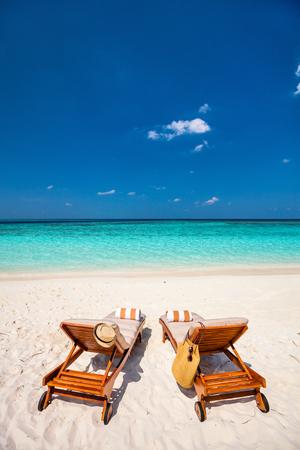 Wooden lounge chairs on a beautiful tropical beach at Maldives Standard-Bild
