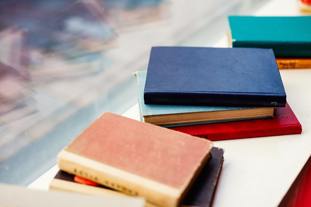 Close up details of old books with colorful covers at flea market