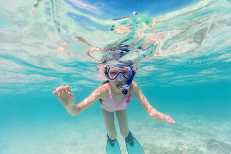 Underwater photo of a little girl swimming in tropical ocean Stock Photo